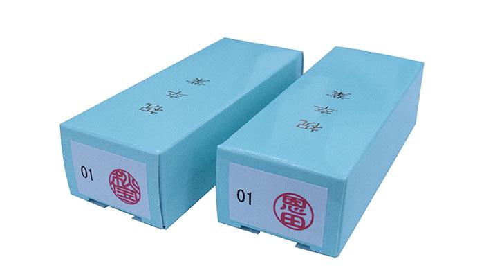包装の上から印鑑の印影シールと出席番号シールを貼っている画像